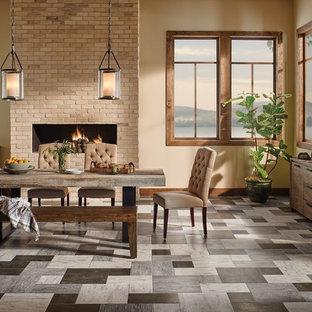 Immagine di una grande sala da pranzo aperta verso il soggiorno rustica con pareti beige, pavimento in vinile, camino lineare Ribbon, cornice del camino in mattoni e pavimento grigio