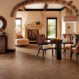 Foto di una sala da pranzo aperta verso il soggiorno rustica di medie dimensioni con pareti beige, pavimento in vinile, camino classico, cornice del camino in intonaco e pavimento marrone