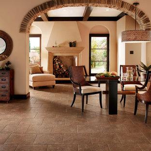 Foto di una grande sala da pranzo aperta verso il soggiorno stile americano con pareti beige, pavimento in gres porcellanato, camino classico, cornice del camino in legno e pavimento marrone