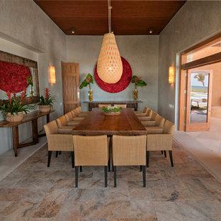Foto di una grande sala da pranzo aperta verso il soggiorno tropicale con pareti grigie e nessun camino