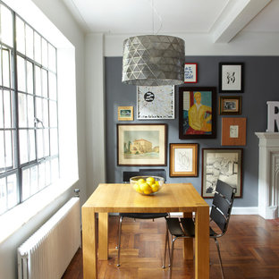 Inspiration for a small industrial medium tone wood floor great room remodel in New York with gray walls, a standard fireplace and a wood fireplace surround