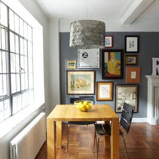 Ejemplo de comedor industrial, pequeño, abierto, con paredes grises, suelo de madera en tonos medios, chimenea tradicional y marco de chimenea de madera