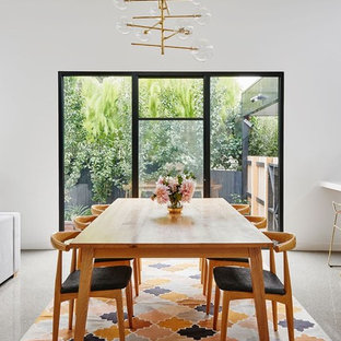 Contemporary open plan dining in Geelong with white walls, concrete floors and grey floor.