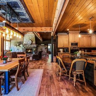 Ejemplo de comedor rural, de tamaño medio, abierto, con paredes marrones, suelo vinílico, chimenea tradicional, marco de chimenea de hormigón y suelo marrón