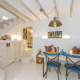 Immagine di una piccola sala da pranzo aperta verso il soggiorno mediterranea con pareti bianche