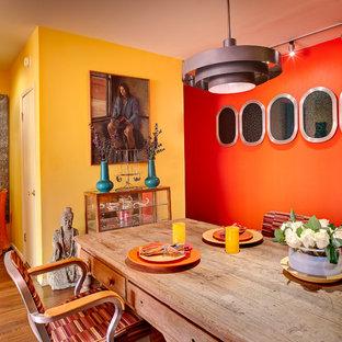 Imagen de comedor bohemio, pequeño, sin chimenea, con suelo de madera en tonos medios y paredes multicolor