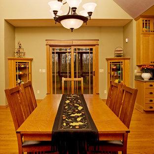 Imagen de comedor de estilo americano, grande, abierto, con paredes verdes y suelo de madera en tonos medios