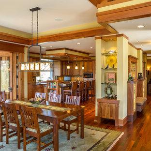Immagine di una sala da pranzo aperta verso la cucina american style con pareti gialle e nessun camino