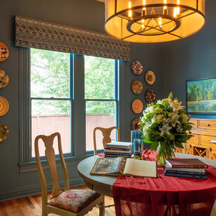 Example of an eclectic medium tone wood floor enclosed dining room design in Austin with blue walls