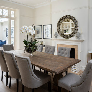 Design ideas for a medium sized classic enclosed dining room in London with beige walls, light hardwood flooring and a standard fireplace.