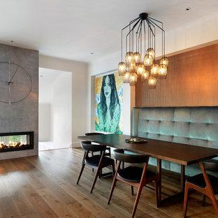 Diseño de comedor actual, grande, con paredes blancas, suelo de madera en tonos medios, chimenea lineal, marco de chimenea de hormigón y suelo marrón