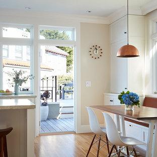 Inspiration pour une salle à manger ouverte sur la cuisine traditionnelle avec un mur blanc, un sol en bois brun et un sol orange.