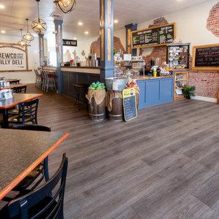 Foto di un'ampia sala da pranzo aperta verso la cucina industriale con pareti multicolore, pavimento in vinile e pavimento grigio