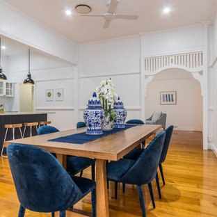 Photo of a beach style kitchen/dining combo in Brisbane with white walls, medium hardwood floors and brown floor.