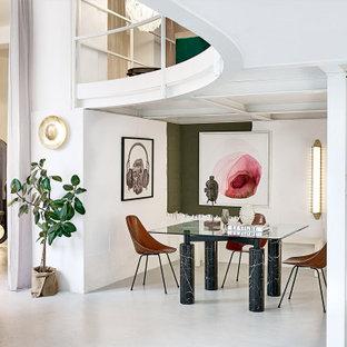 Immagine di una sala da pranzo aperta verso il soggiorno minimal con pareti bianche, pavimento in cemento e pavimento grigio