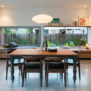This is an example of a midcentury kitchen/dining combo in Brisbane with white walls, concrete floors and grey floor.