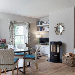 Esempio di una sala da pranzo tradizionale con pareti grigie, pavimento in legno massello medio, stufa a legna e pavimento marrone