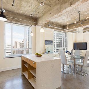 Imagen de comedor urbano, pequeño, abierto, sin chimenea, con paredes beige, suelo de cemento y suelo gris