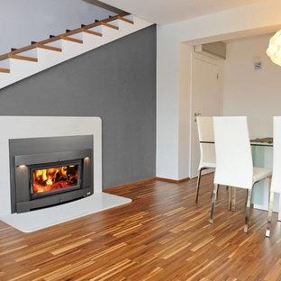 Foto de comedor clásico renovado, de tamaño medio, con paredes grises, suelo de madera en tonos medios, chimenea tradicional, marco de chimenea de metal y suelo marrón