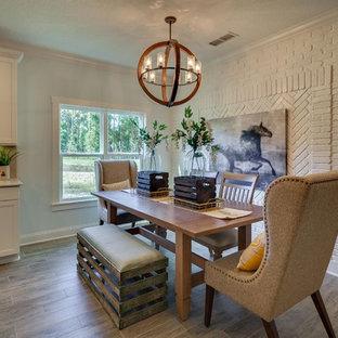 Foto di una sala da pranzo aperta verso la cucina country di medie dimensioni con pareti bianche, pavimento in laminato e nessun camino