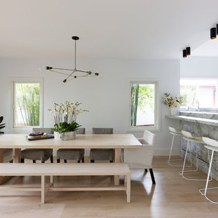 This is an example of a contemporary kitchen/dining combo in Sydney with white walls, light hardwood floors and beige floor.