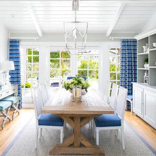 Immagine di una sala da pranzo costiera con pareti bianche e pavimento in legno massello medio