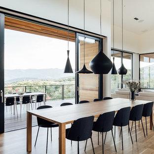 Foto de comedor minimalista, abierto, con paredes blancas, suelo de madera clara y suelo beige