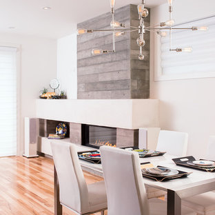 Cette image montre une salle à manger design avec un mur blanc, un sol en bois brun, une cheminée ribbon et un manteau de cheminée en béton.