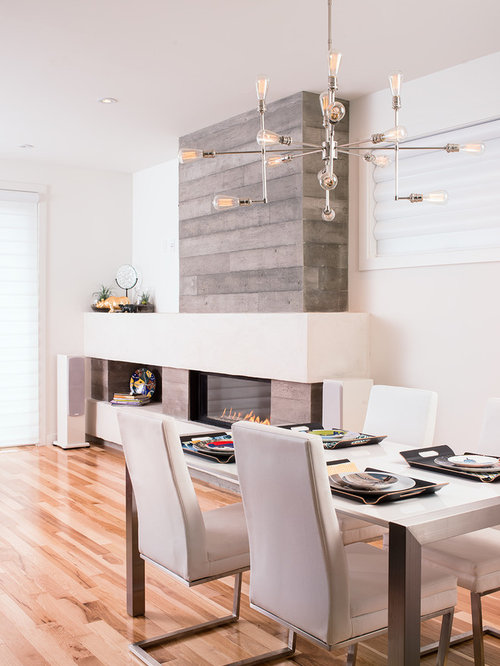 Example Of A Trendy Medium Tone Wood Floor Dining Room Design In Calgary With White Walls
