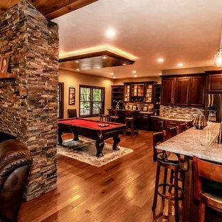 Immagine di una grande sala da pranzo aperta verso la cucina con pareti beige, parquet chiaro, camino bifacciale, cornice del camino in pietra e pavimento blu