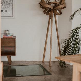 Bild på en mellanstor eklektisk matplats med öppen planlösning, med vita väggar, betonggolv, en öppen vedspis och grått golv