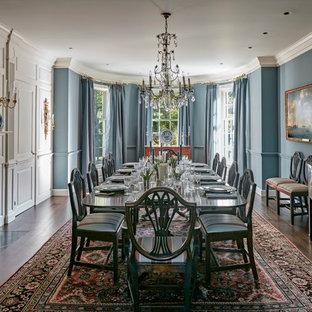 Пример оригинального дизайна: большая отдельная столовая в классическом стиле с синими стенами, темным паркетным полом, стандартным камином и фасадом камина из плитки