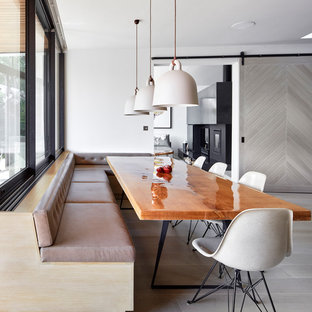 Inspiration for a contemporary kitchen/dining room in London with white walls, light hardwood flooring and grey floors.
