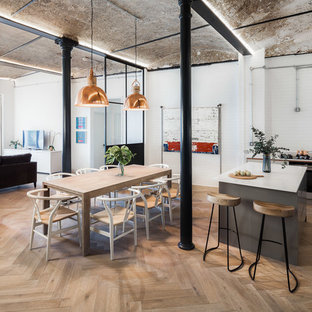 Photo of an urban kitchen/dining room in London with white walls, medium hardwood flooring and brown floors.