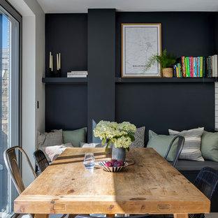 Immagine di una sala da pranzo contemporanea con pavimento con piastrelle in ceramica, pavimento grigio e pareti nere
