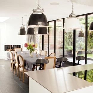 Modelo de comedor de cocina contemporáneo, grande, con paredes blancas, suelo gris y chimenea de esquina