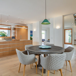 Kitchen/dining room combo - tropical light wood floor and beige floor kitchen/dining room combo idea in Los Angeles with white walls