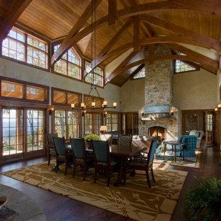 Ejemplo de comedor rural, grande, abierto, con paredes beige, suelo de madera oscura, chimenea tradicional y marco de chimenea de ladrillo