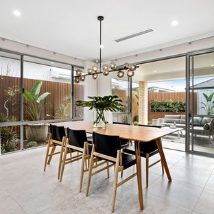 Photo of a mid-sized contemporary open plan dining in Perth with beige walls and beige floor.