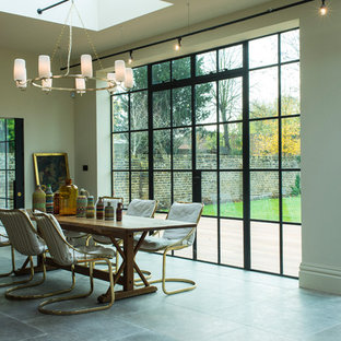 Large modern open plan dining room in Sussex with white walls and grey floors.