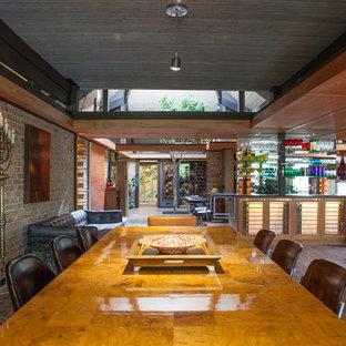Immagine di una grande sala da pranzo aperta verso il soggiorno eclettica con pareti beige e pavimento in mattoni