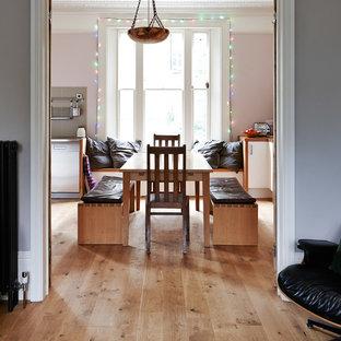 На фото: столовая среднего размера в стиле фьюжн с паркетным полом среднего тона и розовыми стенами с