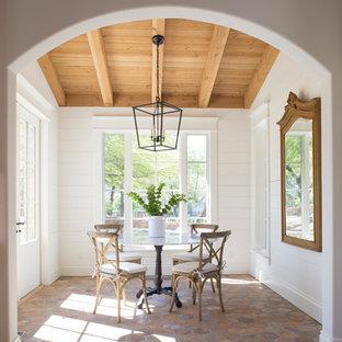 Imagen de comedor campestre, cerrado, sin chimenea, con paredes blancas, suelo de baldosas de terracota y suelo rojo