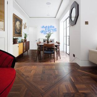 Foto di una sala da pranzo design con pareti bianche, pavimento in sughero e camino classico