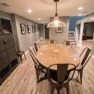 Foto di una sala da pranzo aperta verso la cucina stile rurale di medie dimensioni con pareti grigie, pavimento in vinile, camino sospeso e pavimento marrone