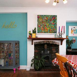 Foto di una sala da pranzo aperta verso la cucina eclettica di medie dimensioni con pareti multicolore, parquet scuro, stufa a legna, cornice del camino in legno e pavimento marrone