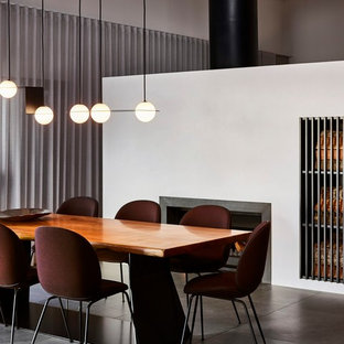 Contemporary dining room in Brisbane with white walls, a standard fireplace and grey floor.