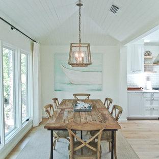 Ejemplo de comedor costero, pequeño, con paredes blancas y suelo de madera clara