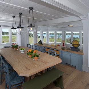 Bild på ett stort amerikanskt kök med matplats, med vita väggar, ljust trägolv och brunt golv