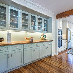 Exemple d'une grande salle à manger ouverte sur la cuisine chic avec un sol en bambou, un mur blanc et aucune cheminée.